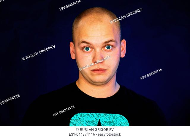 young guy balding in a vest on a dark background