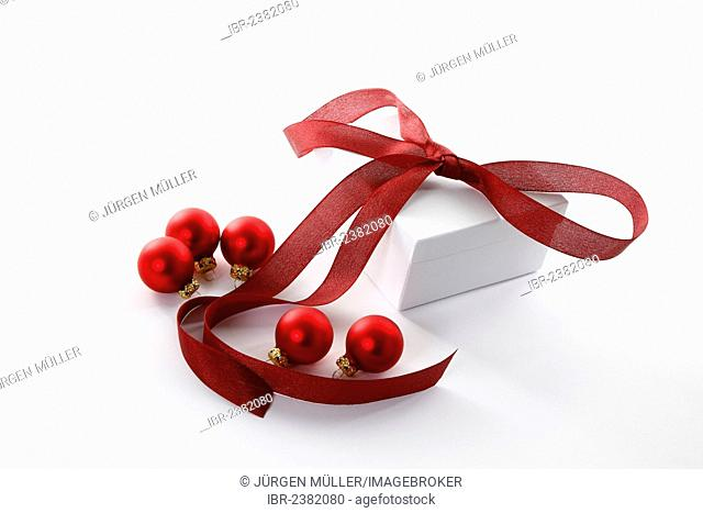 Red Christmas baubles and a present with a red ribbon