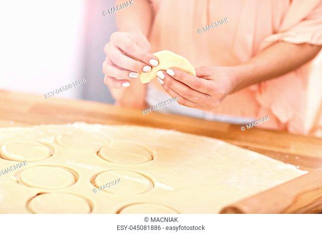 Portrait of young woman trying to make pierogi in kitchen