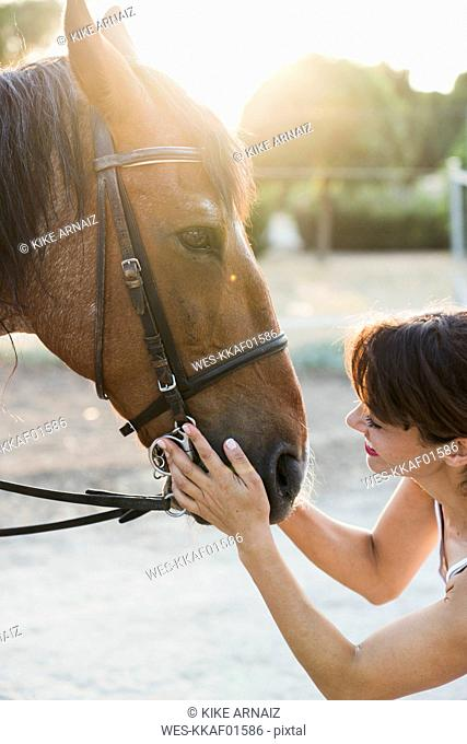 Smiling woman stroking horse