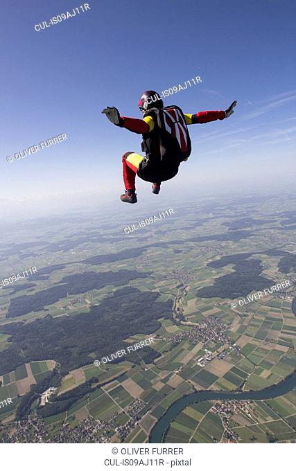 Female skydiver free falling over Grenchen, Berne, Switzerland