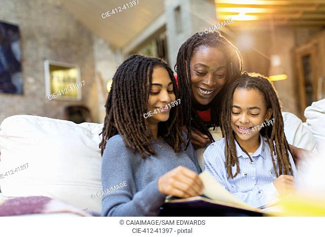 Mother and daughters looking at photo album on sofa