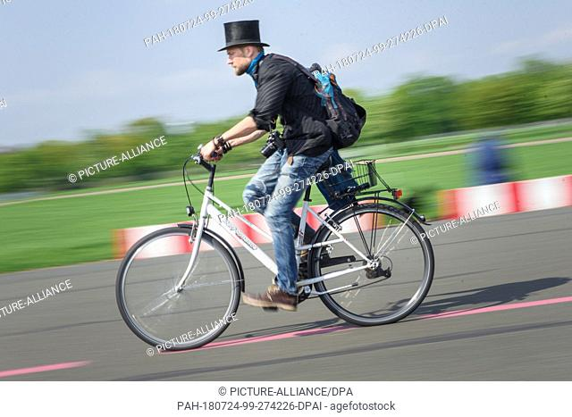 23 April 2018, Germany, Berlin: Juha Jaervinen, participant of the experiment Basic Income in Finland, rides a rented bicycle over a runway at the former...