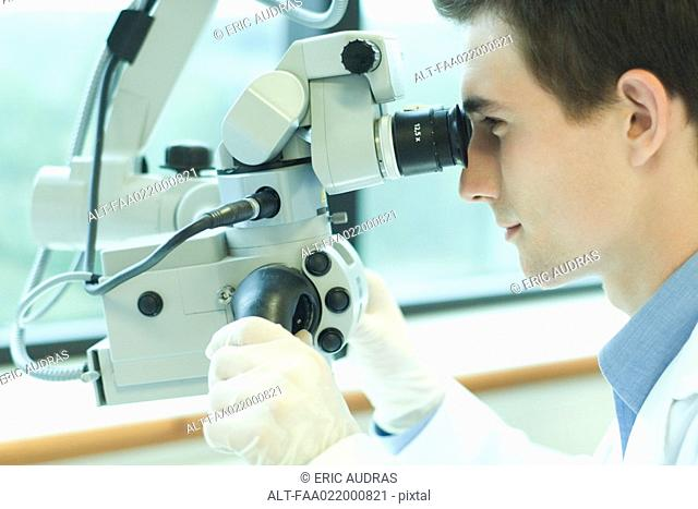 Young male scientist looking through microscope