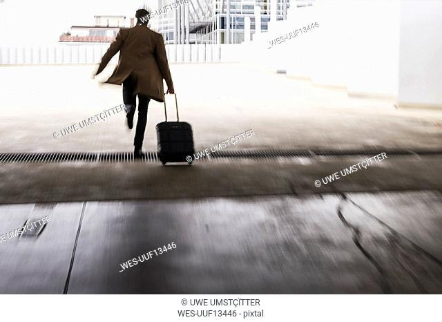 Businessman with rolling suitcase in a hurry at parking garage