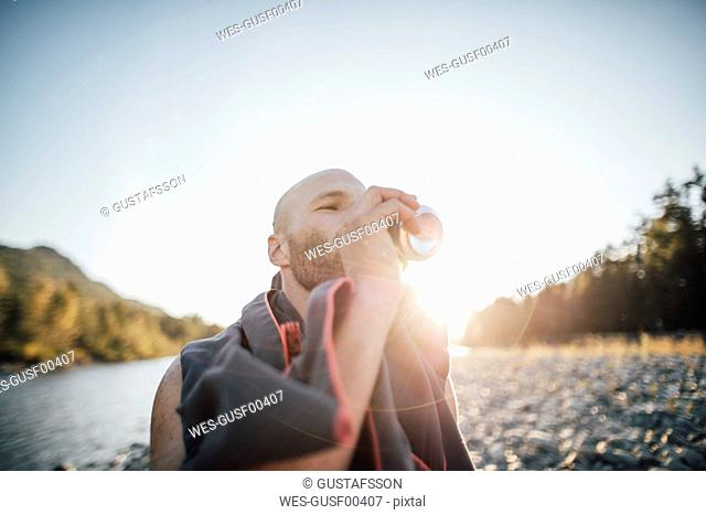 Canada, British Columbia, Chilliwack, man drinking from can at Fraser River