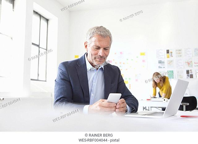 Businessman in office at desk looking at cell phone