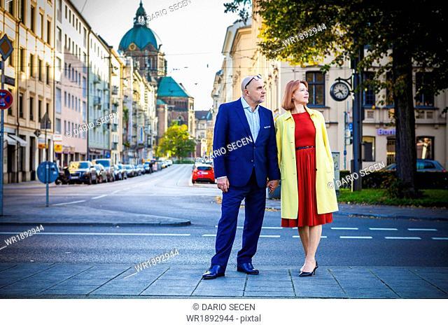 Senior couple holding hands on city street, Munich, Bavaria, Germany