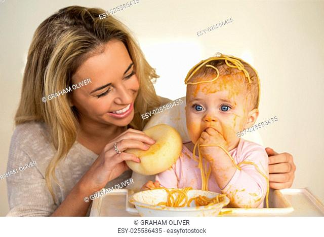 Mother laughing as she tries to clean her messy baby daughter, who has tipped spaghetti over her head