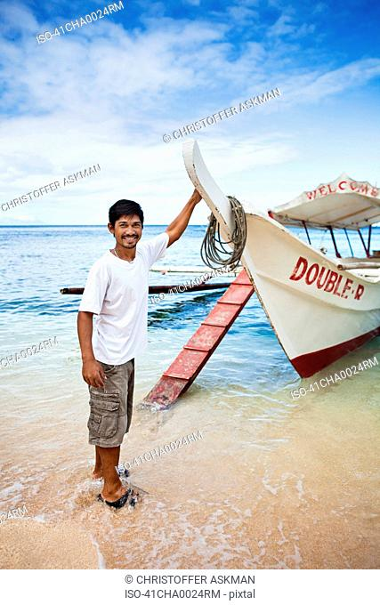 Man with boat on tropical beach
