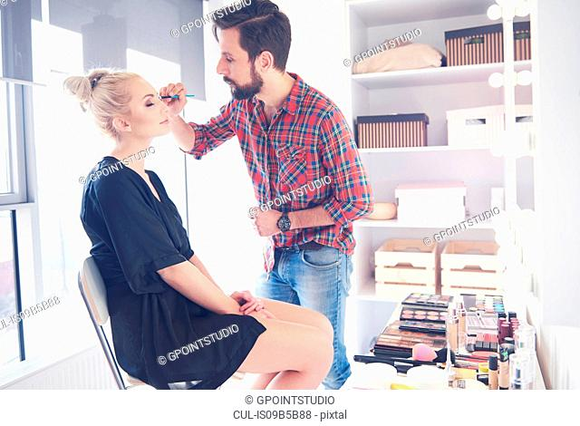 Male make up artist applying eyeliner to model for photo shoot