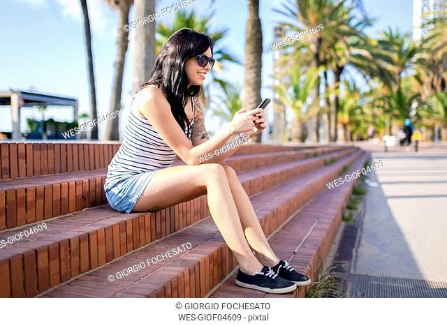 Spain, Barcelona, smiling young woman sitting on steps at sunlight using cell phone