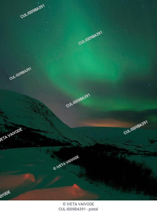 Aurora borealis over snow covered hills at night, Finnmark, Norway