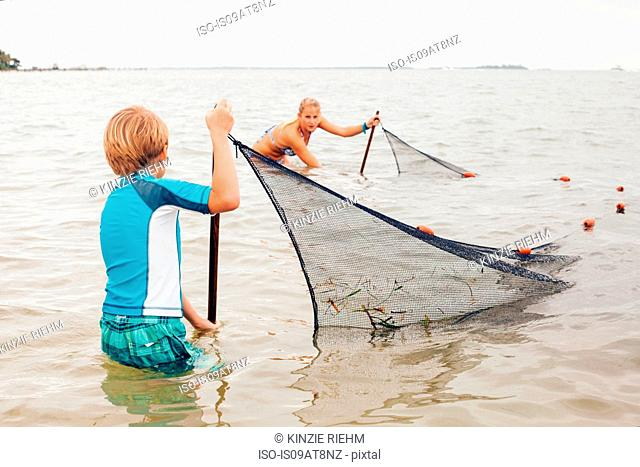 Kids in water using fishing net, Sanibel Island, Pine Island Sound, Florida, USA