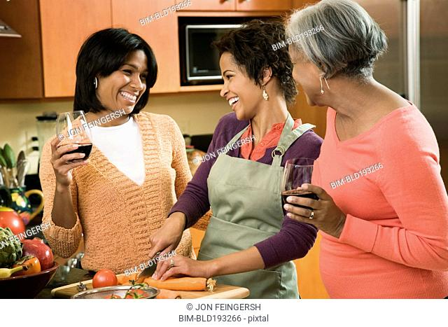 African American mother and daughters cooking and talking in kitchen