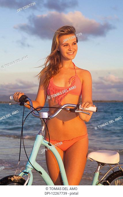 Teenage girl at the beach with her bike; Kailua, Island of Hawaii, Hawaii, United States of America