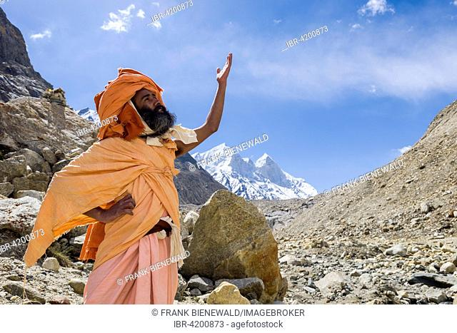 A Sadhu, holy man, is standing and praying at Gaumukh, the main source of the holy river Ganges, Gangotri, Uttarakhand, India
