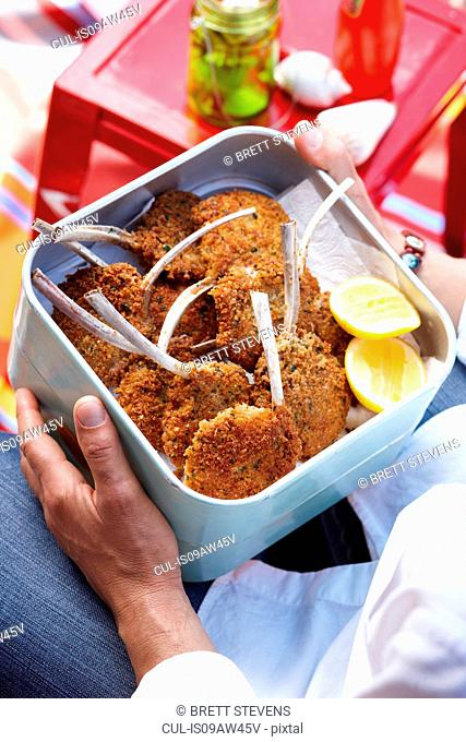 High angle view of mid adult man holding container of parmesan lamb cutlets