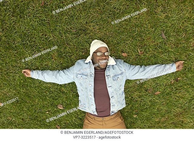 laughing man laying on meadow, relaxing, happy, in Munich, Germany