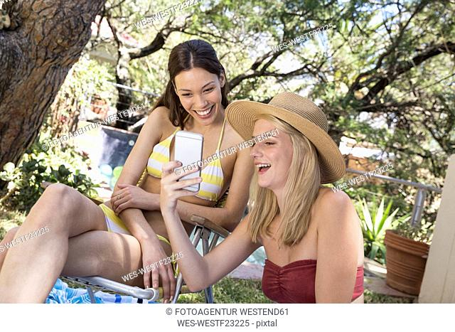 Two happy young women in garden sharing cell phone