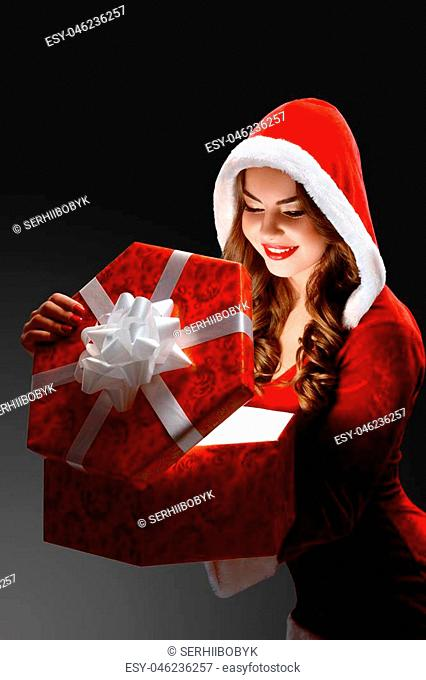 Young beatiful Snow Maiden in the red suit opens a big red gift for New Year 2018, 2019 and Christmas. She has pretty, smiling face and brown curly hair