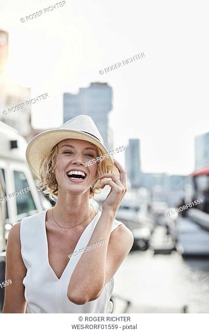 Portrait of laughing young woman wearing a hat at a marina