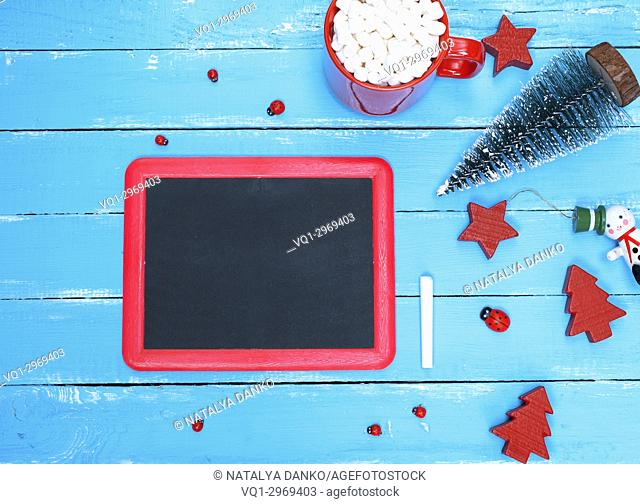 black chalkboard in a red frame on a blue wooden background and a red mug of hot chocolate