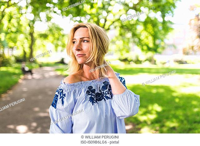 Mature woman with hand in blond hair looking over her shoulder in park