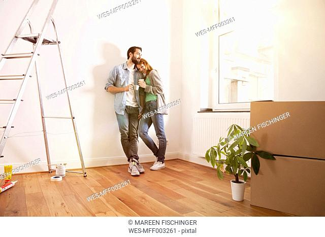 Smiling young couple having a coffee break in new apartment