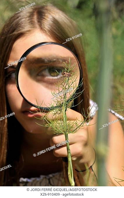girl with magnifying glass in a natural science class in the field