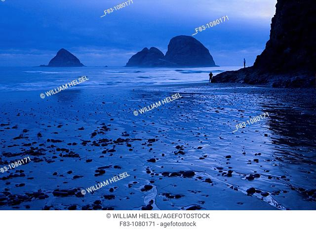 USA, Oregon, Tillamook County, Oceanside, sea stacks, beach and cliff, dusk, low tide, people, August