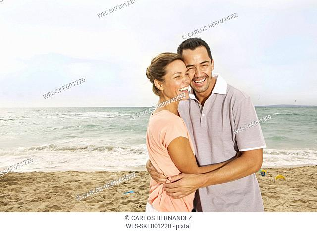 Spain, Mid adult couple on beach at Palma de Mallorca, smiling