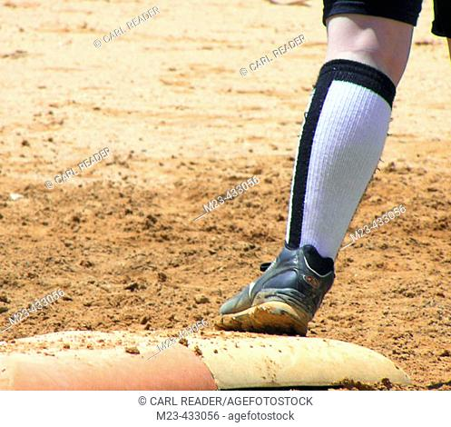 A softball runner's foot remains safely on base