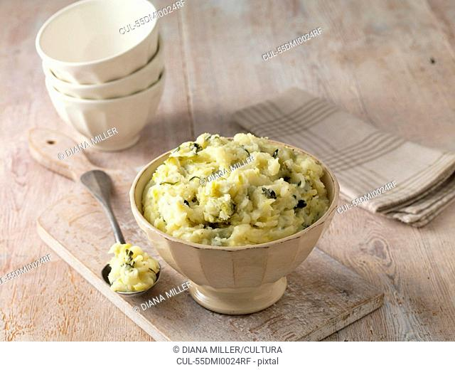 Colcannon potato mash in cream faceted bowl with metal spoon