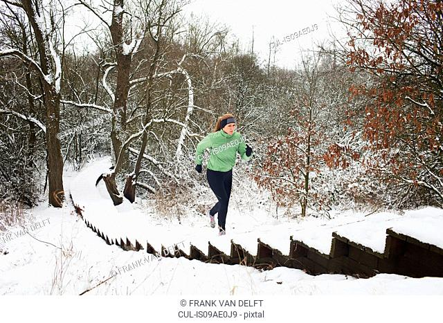 Female runner moving up snow covered staircase in winter