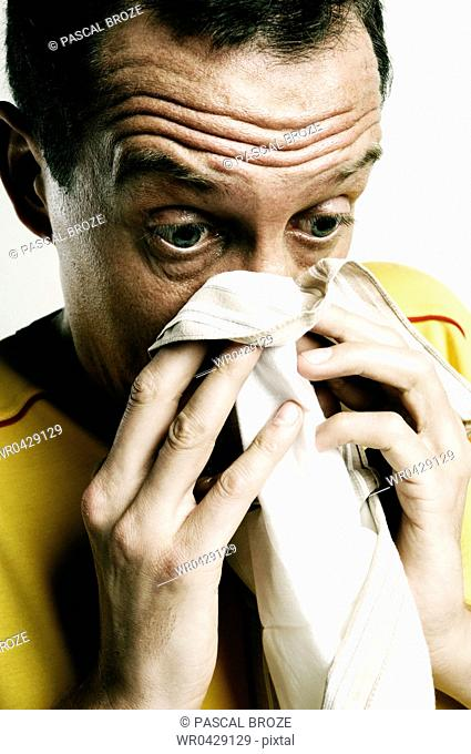 Mid adult man blowing his nose on a handkerchief