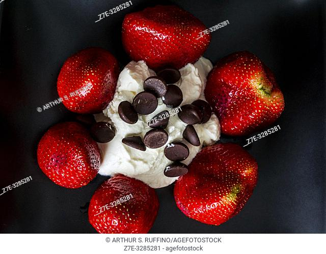 Greek yogurt encircled by whole strawberries and topped with chocolate chips. Macro image against black background