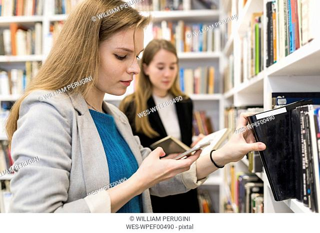 Portrait of teenage girl looking at cell phone while taking book of shelf in a public library