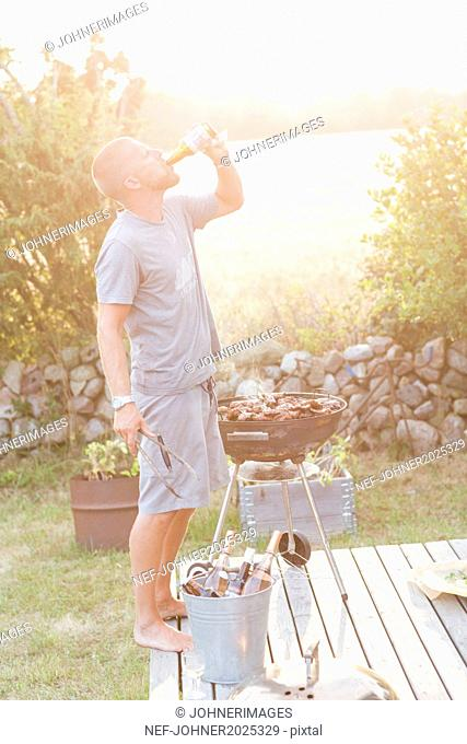 Man drinking beer while having barbecue
