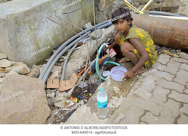 an homeless girl steal water from the public water pipe. sakinaka district. mumbay. maharashtra. india. asia