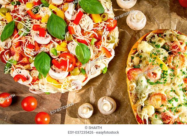 Closeup of baked pizza and raw with vegetables