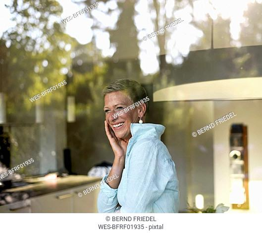 Portrait of laughing woman looking out of window
