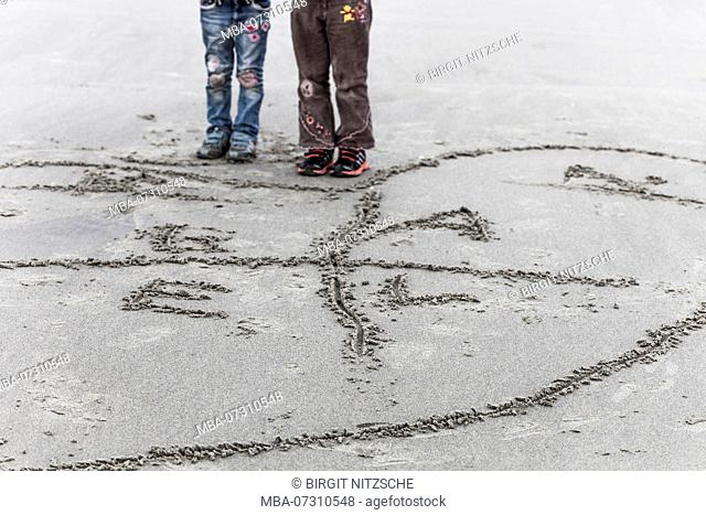 Children's legs in front of sand drawing