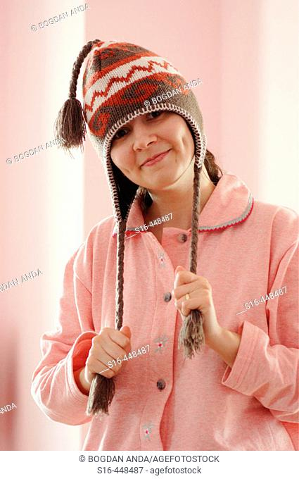 Portrait of a happy beautiful young woman dressed in pyjamas and wearing a funny hat