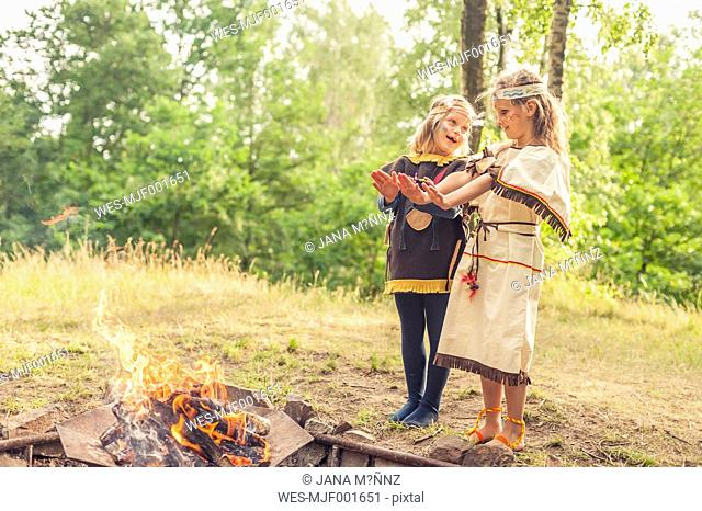 Germany, Saxony, Indians and cowboy party, Girls standing at fire, warming hands