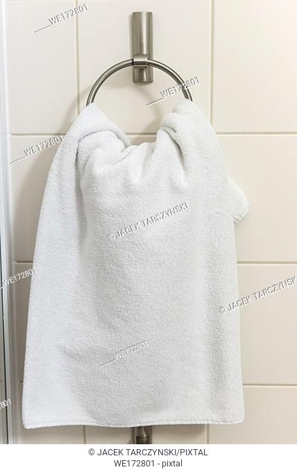 white towel on a hanger in bathroom