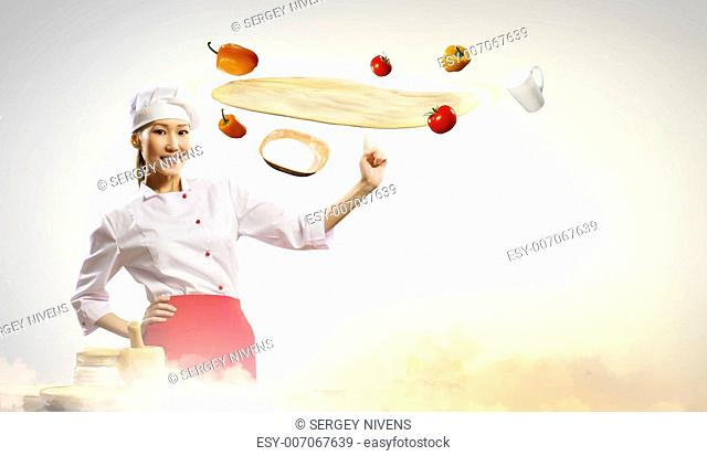 Asian female cook making pizza standing against color background