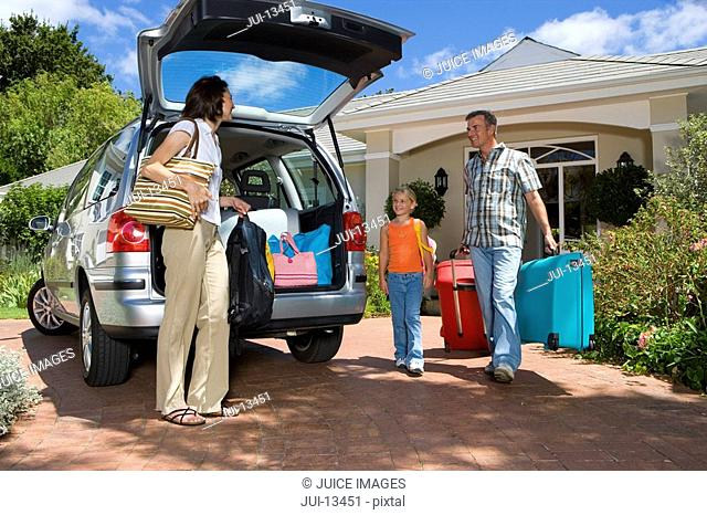Family of three loading boot of car with luggage, low angle view