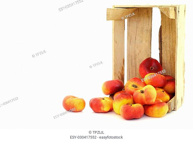 flat nectarines in a wooden crate on a white background