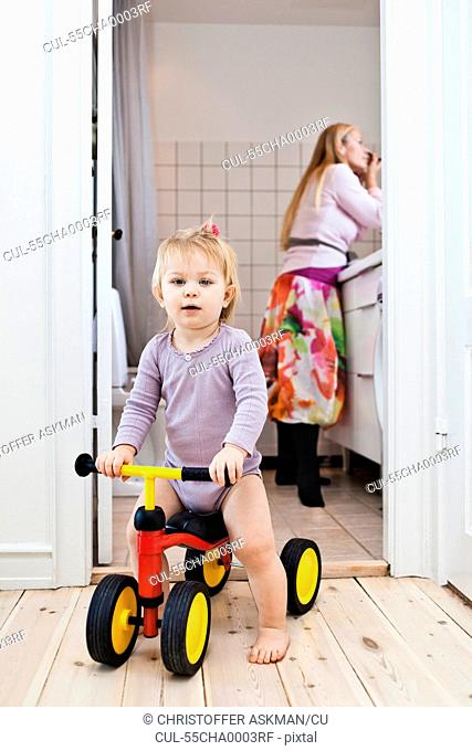 Toddler girl playing on tricycle, mother in background